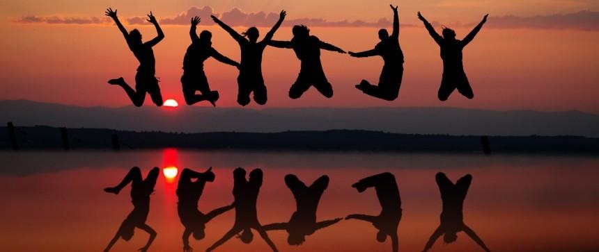 Vrais amis sautent dans le coucher de soleil